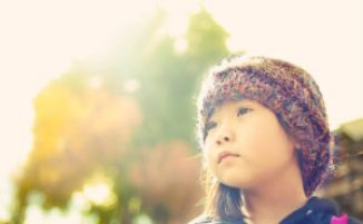 girl looking off into the sun - discussing the scary stuff with your kids