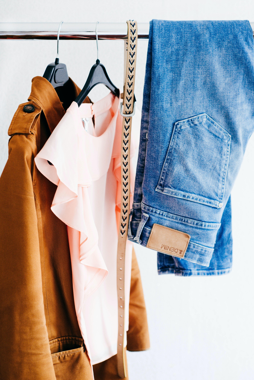 shirt jacket, belt and jeans hanging over a rack