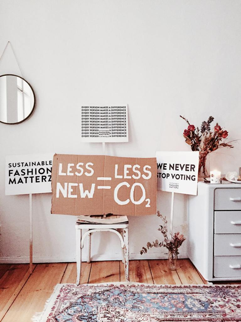 cardboard sign in white room that promotes eco-friendly consumerism and anti consumerism.