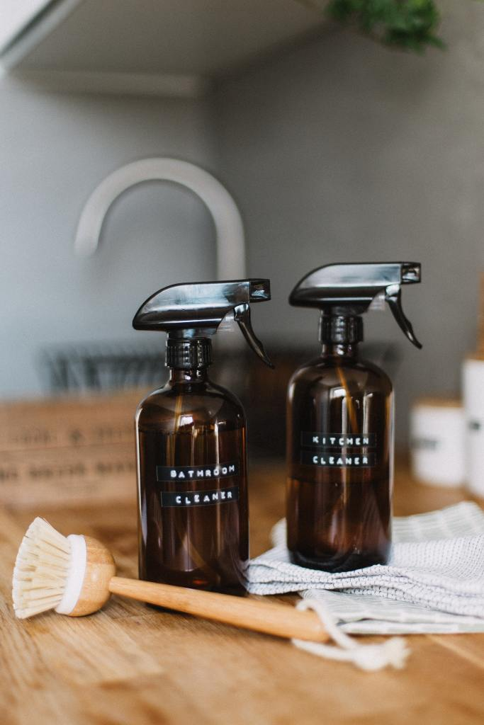 two glass bottles for homemade cleaners for the kitchen and bathroom with a bamboo scrub brush