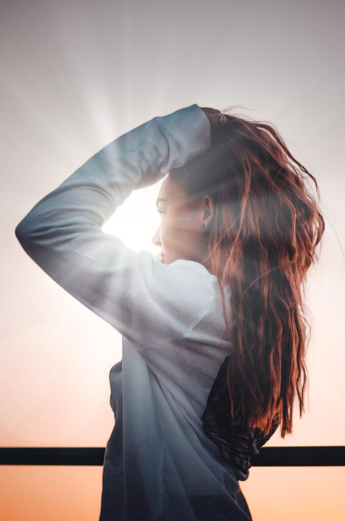 woman stand in sunlight with long beautiful hair