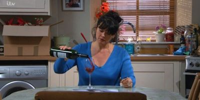 Moira Dingle in Emmerdale pouring a large glass of wine