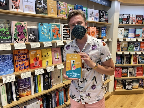 Justin Myers holding copy of The Magnificent Sons in a bookshop