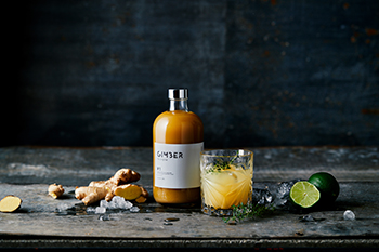 A bottle of Gimber with some ginger and a cucumber nearby on a lovely chopping board