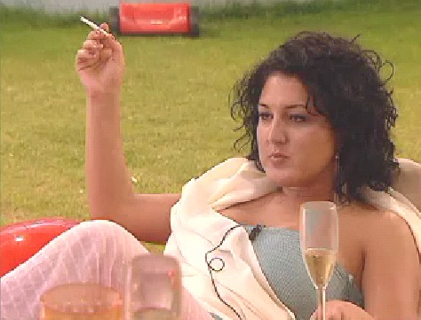 Nadia from Big Brother holding a glass of champagne and a cigarette and looking annoyed
