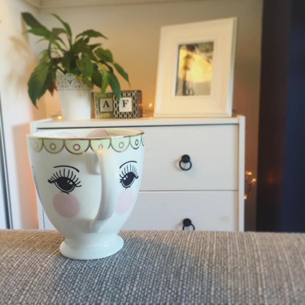 Mug with face and living room in background