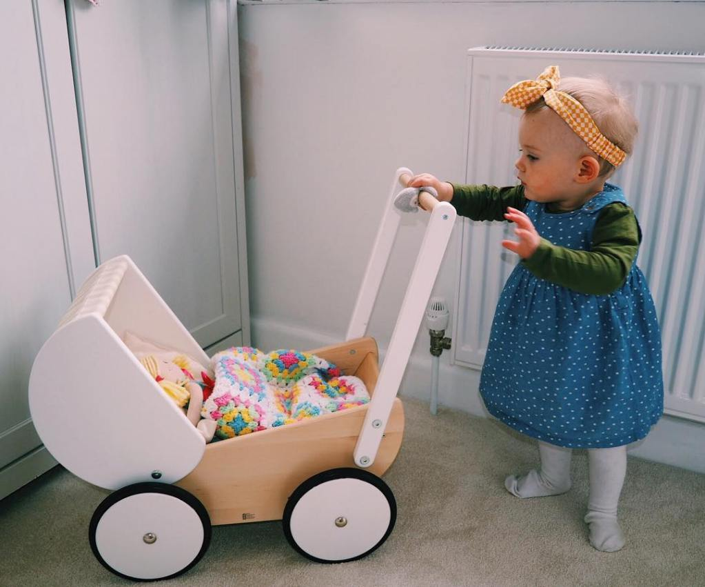 little girl with white wooden pram and yellow head scarf