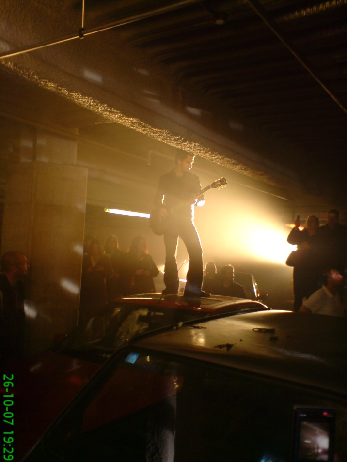 Kelly Jones standing on car with guitar