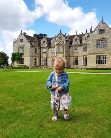 one year old girl standing in front of manor house in background with necklace in hand