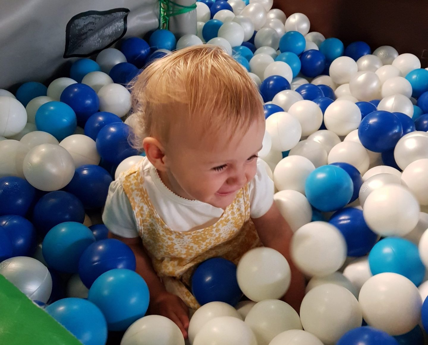 Ettie in ball pit with blue and white balls