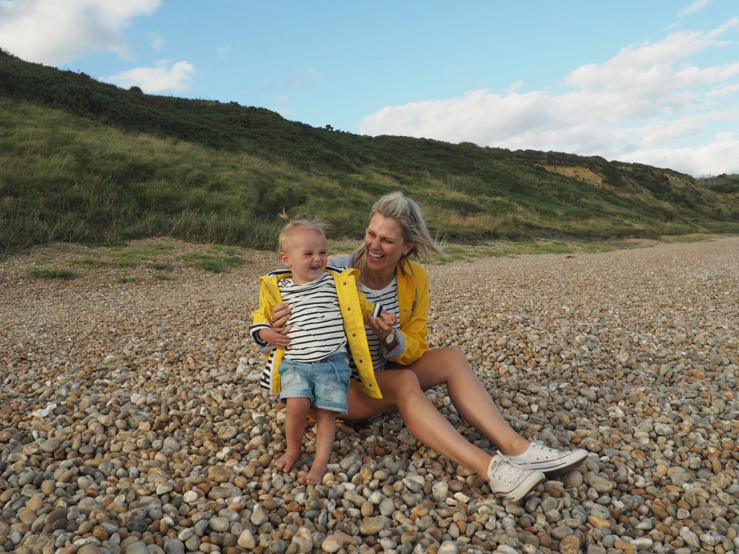 mother and daughter in matching yellow raincoats smiling on shingle beach