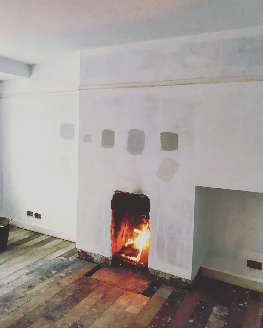 fire in living room with bare walls and wooden floor
