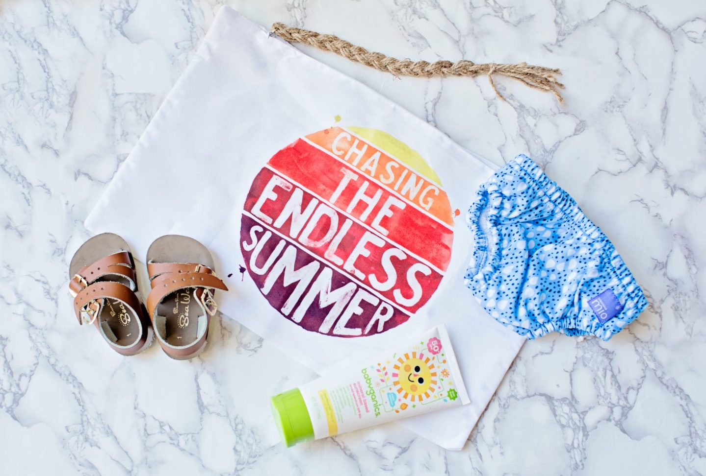 baby sandles, sun tan lotion and sunscreen with bag saying ' chasing the endless summer'