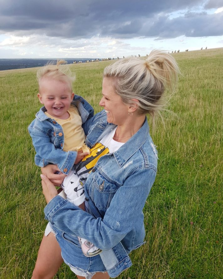 Mother and one year old daughter in denim jackets in green field both smiling