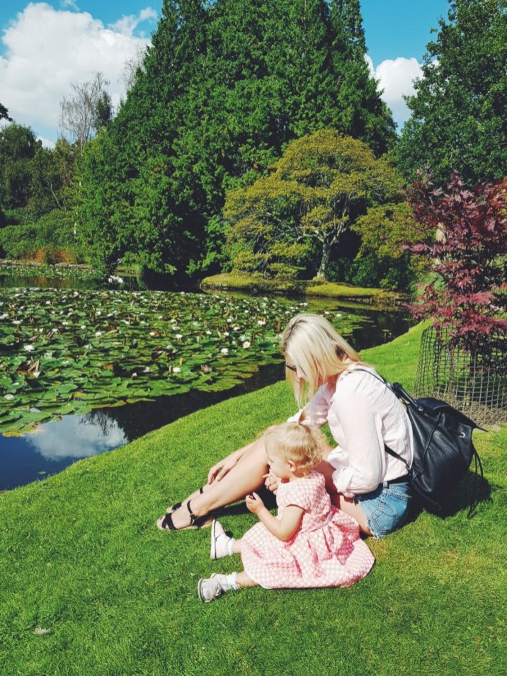 mother and daughter sitting by duck pond at Sheffield Park