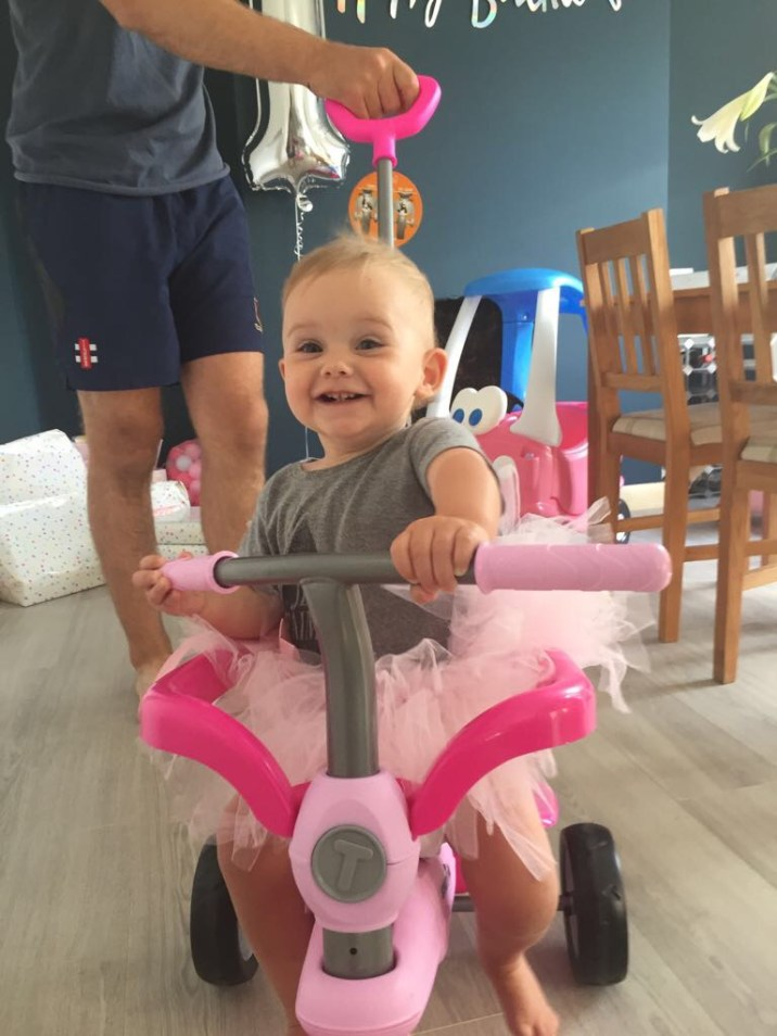 one year old girl smiling on pink trike