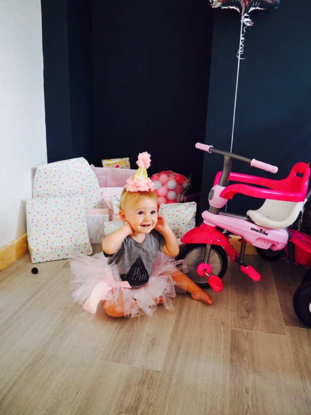 little girl sitting on floor in front of pink trike