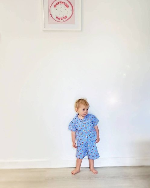 one year old girl in blue PJs against white wall