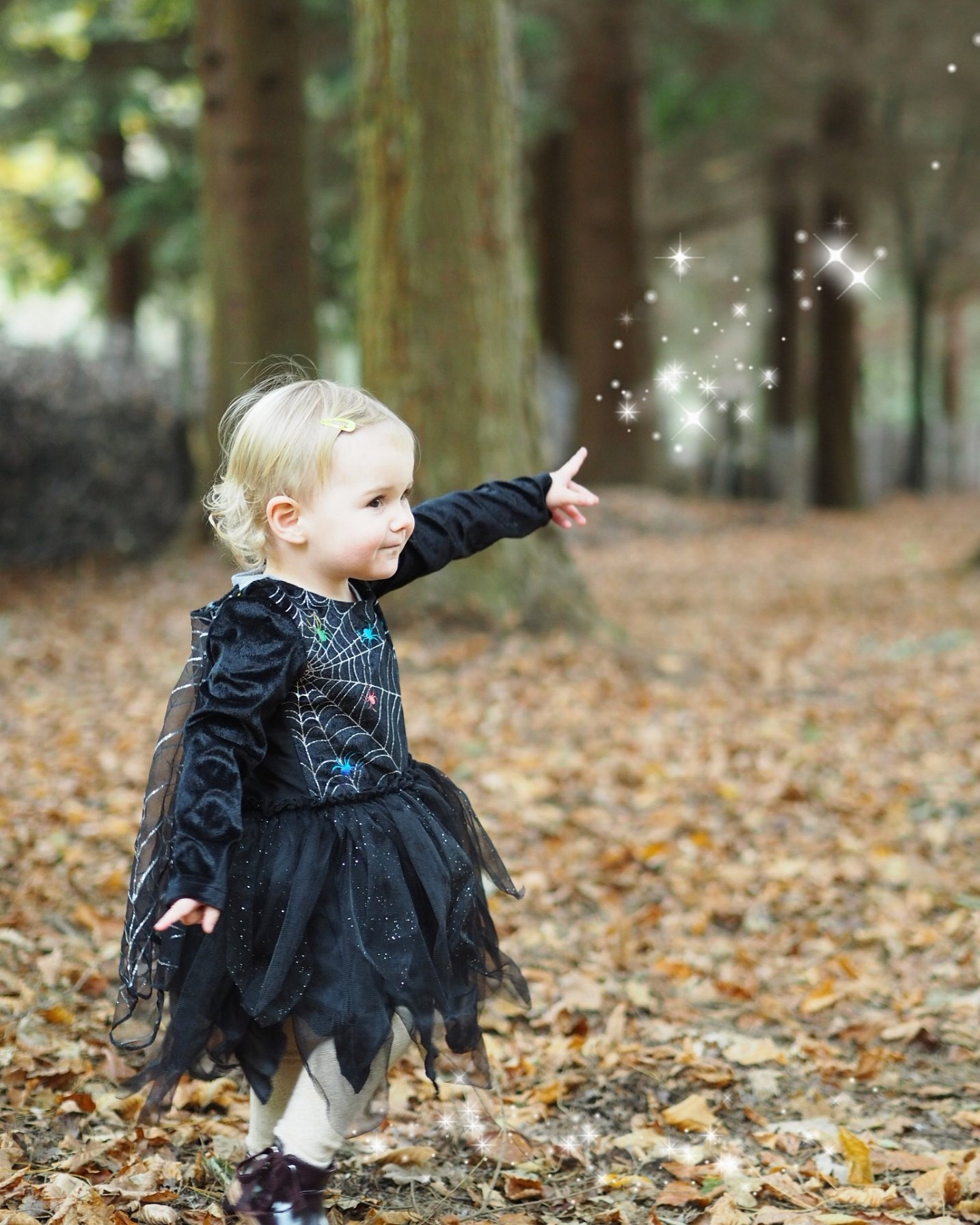 little girl in witches outfit in the woods