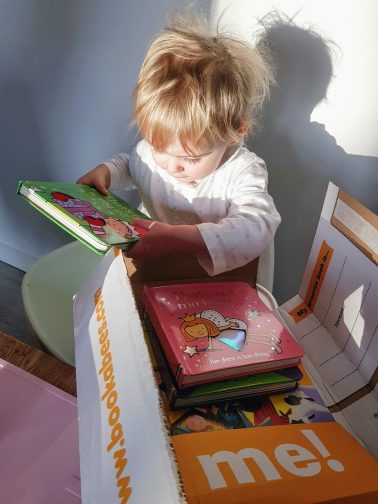 1 year old girl opening the bookabees box