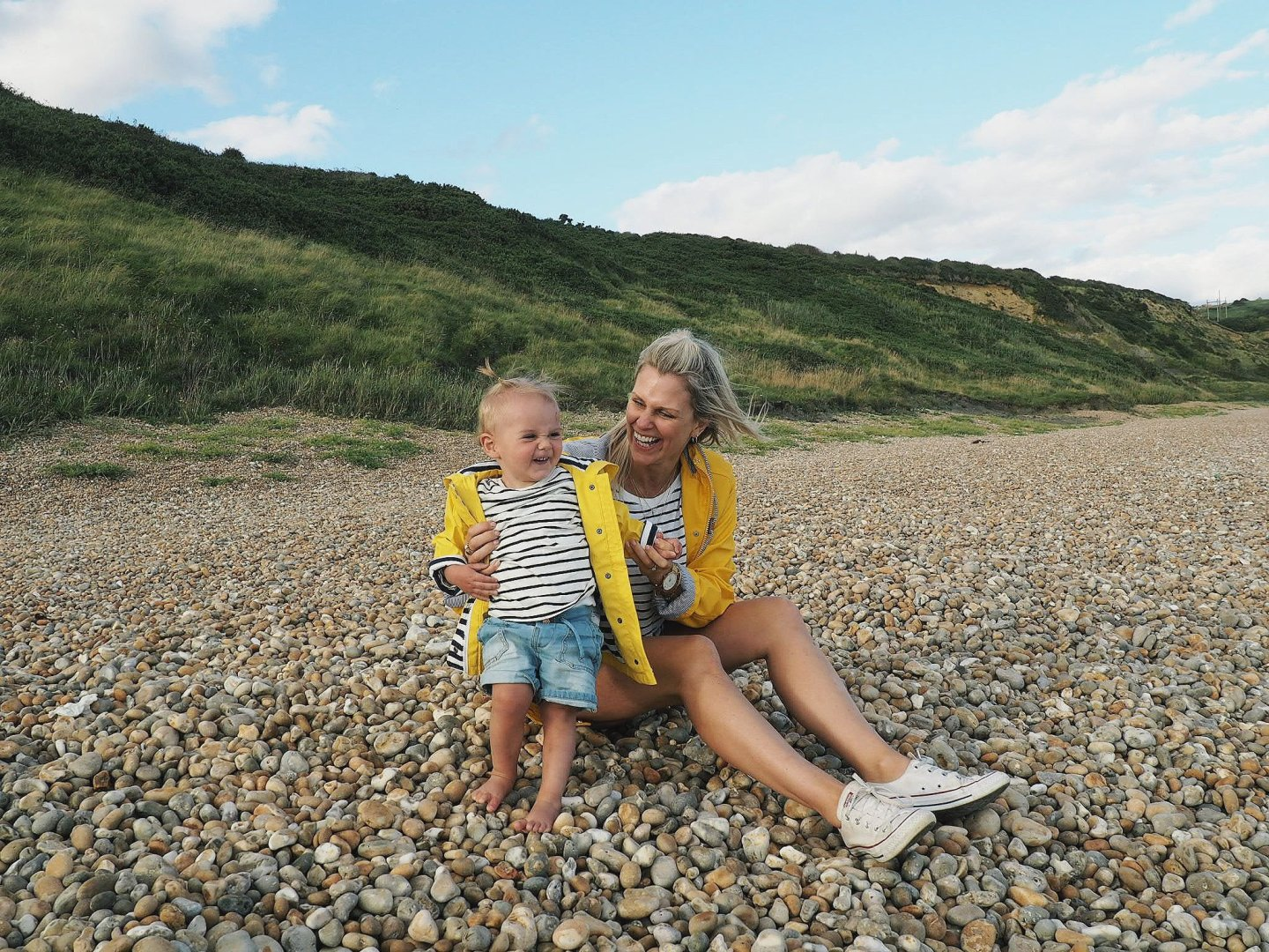 The Essential guide to camping with a baby | mummy and daughter on beach in matching yellow coats