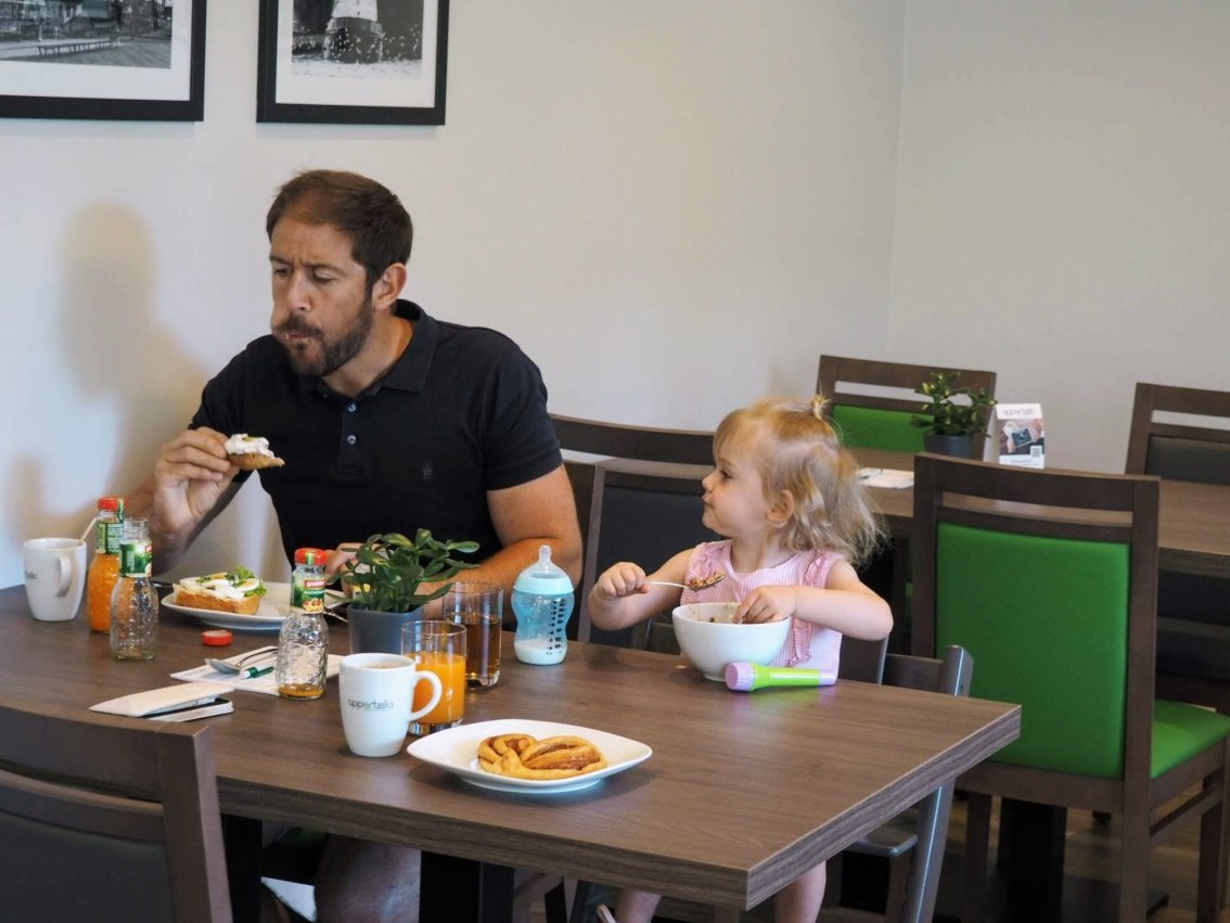 FAther eating breakfast with daughter   Hamburg with a toddler