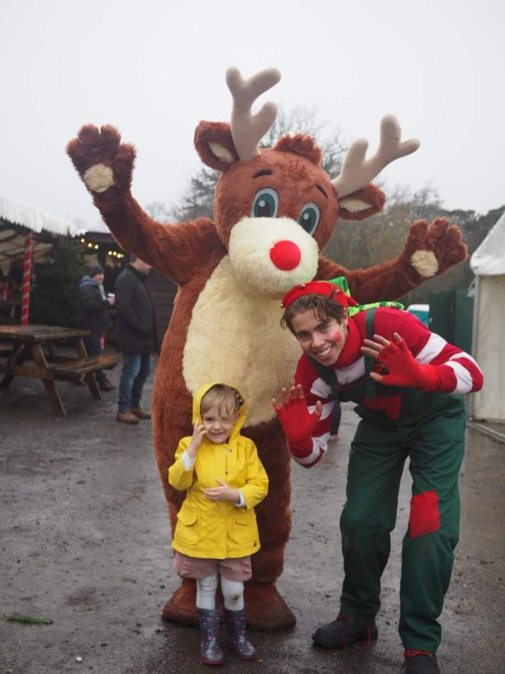 Little girl with Elf and Reindeer at Tulleys Farm at Christmas