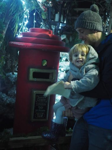 girl with Dad posting a letter to santa in a postbox at Tulleys Farm at Christmas