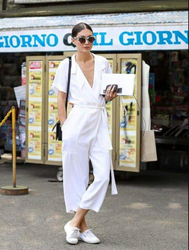 dark haired lady in white jumpsuit and white trainers