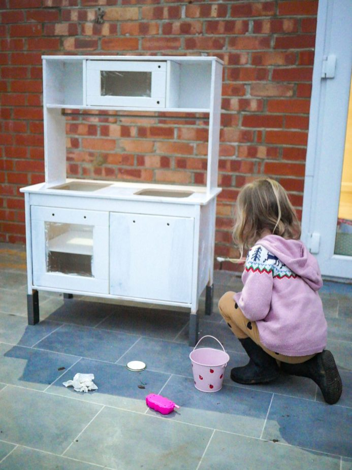 3 year old girl painting stripped down Ikea Play Kitchen