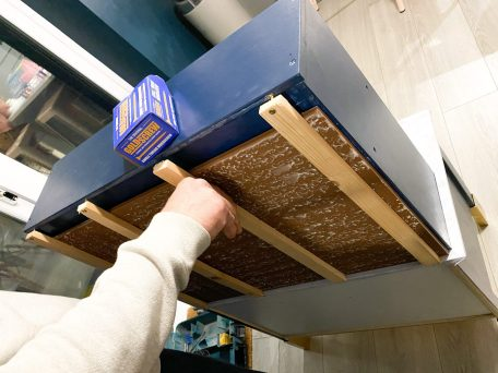 Man affixing wooden batons to back of Ikea Duktig play kitchen