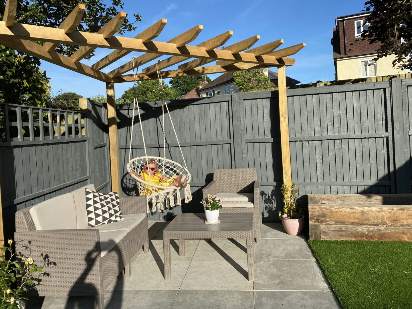 hanging chair in patio area with pergola and grey fence