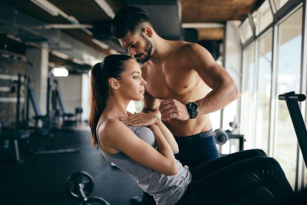 Beneficios de tener un entrenador personal - personal-trainer-giving-instructions-in-gym-c5fgun4