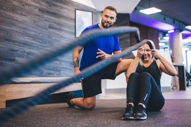 Beneficios de tener un entrenador personal - young-woman-exercising-with-personal-trainer-at-cen6g7s