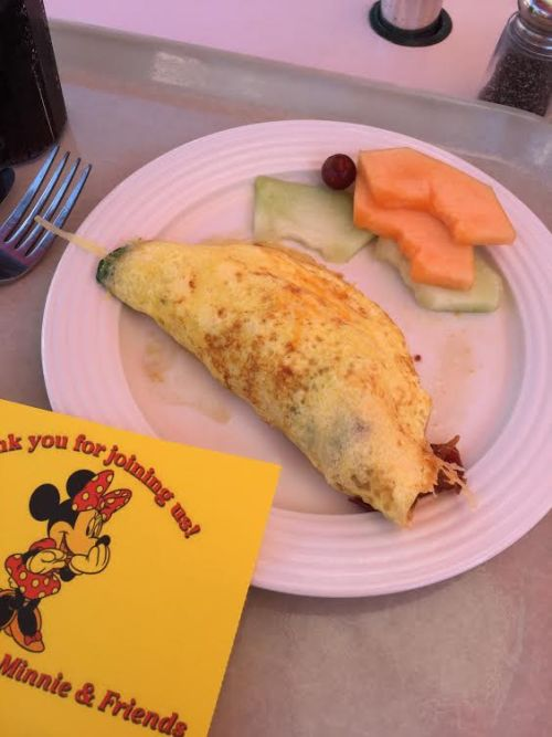 Vegetable omelet with cantaloupe, honey dew melon and red grape next to a picture of Minnie Mouse.