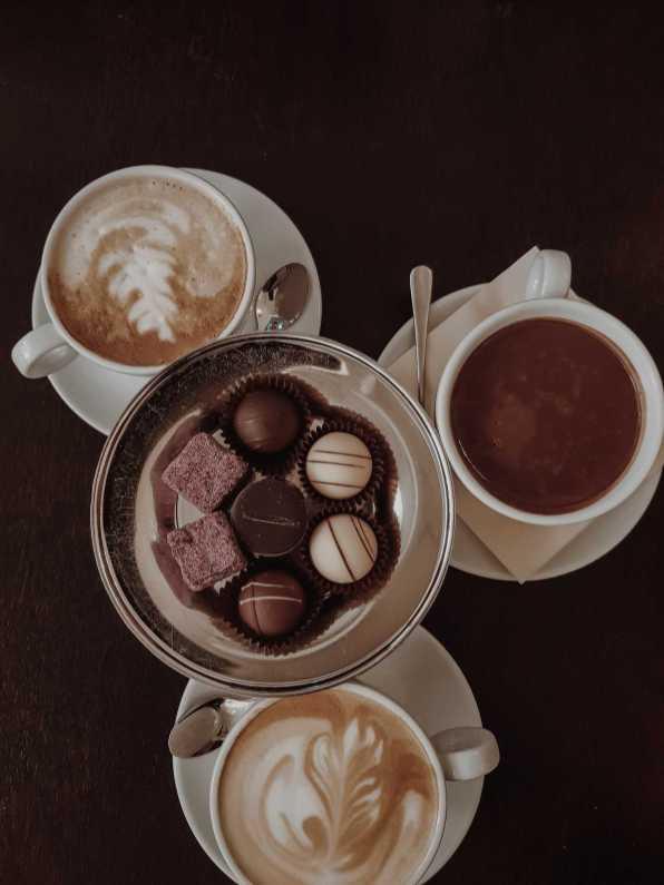 Pralinen auf Silbertablett und Cappuccino in Café