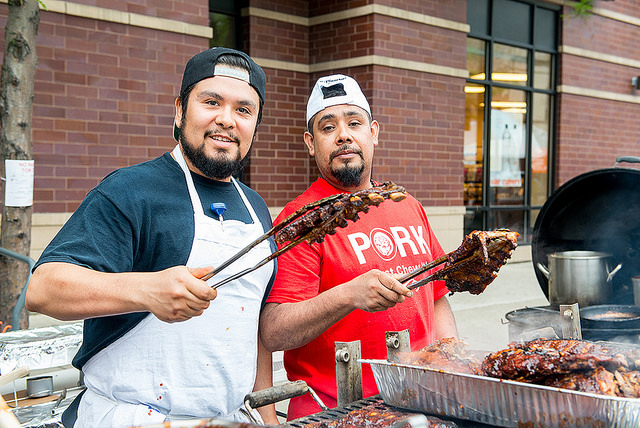 Two-Men-Holding-Rack-Of-Ribs-At-A-Food-Festival