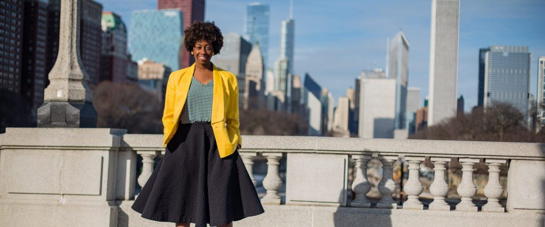 Taylor Justin also known as The Haute Seeker in a yellow blazer with her back facing the Chicago Skyline
