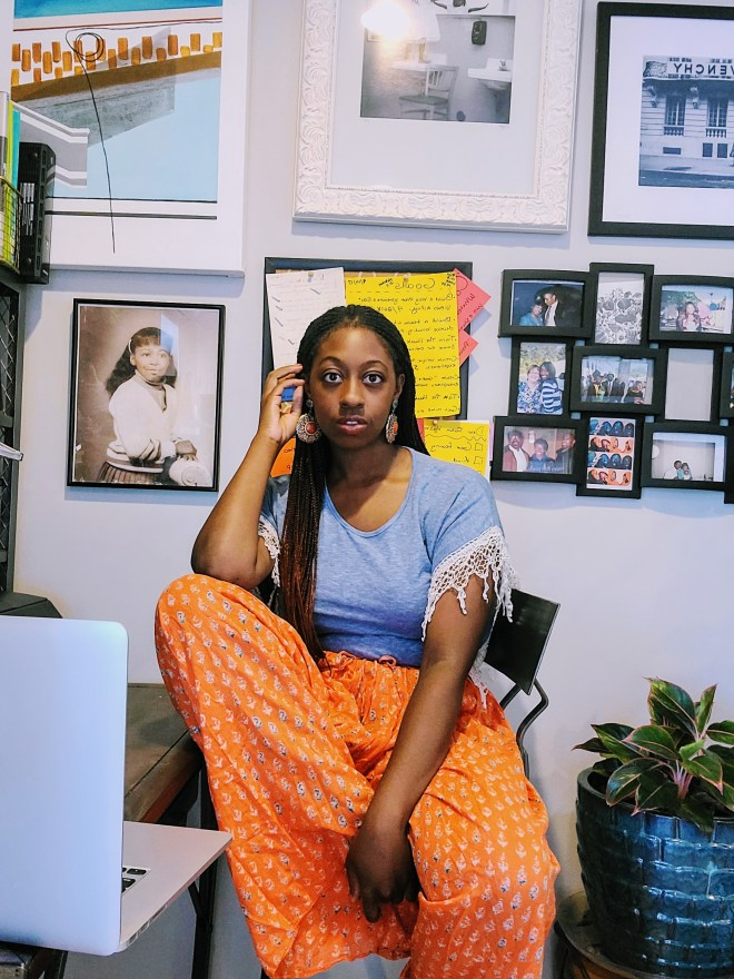 Black girl working from home office in Work from Home outfit inspiration blue T-shirt with fringe sleeves and orange floral pants as seen on The Haute Seeker