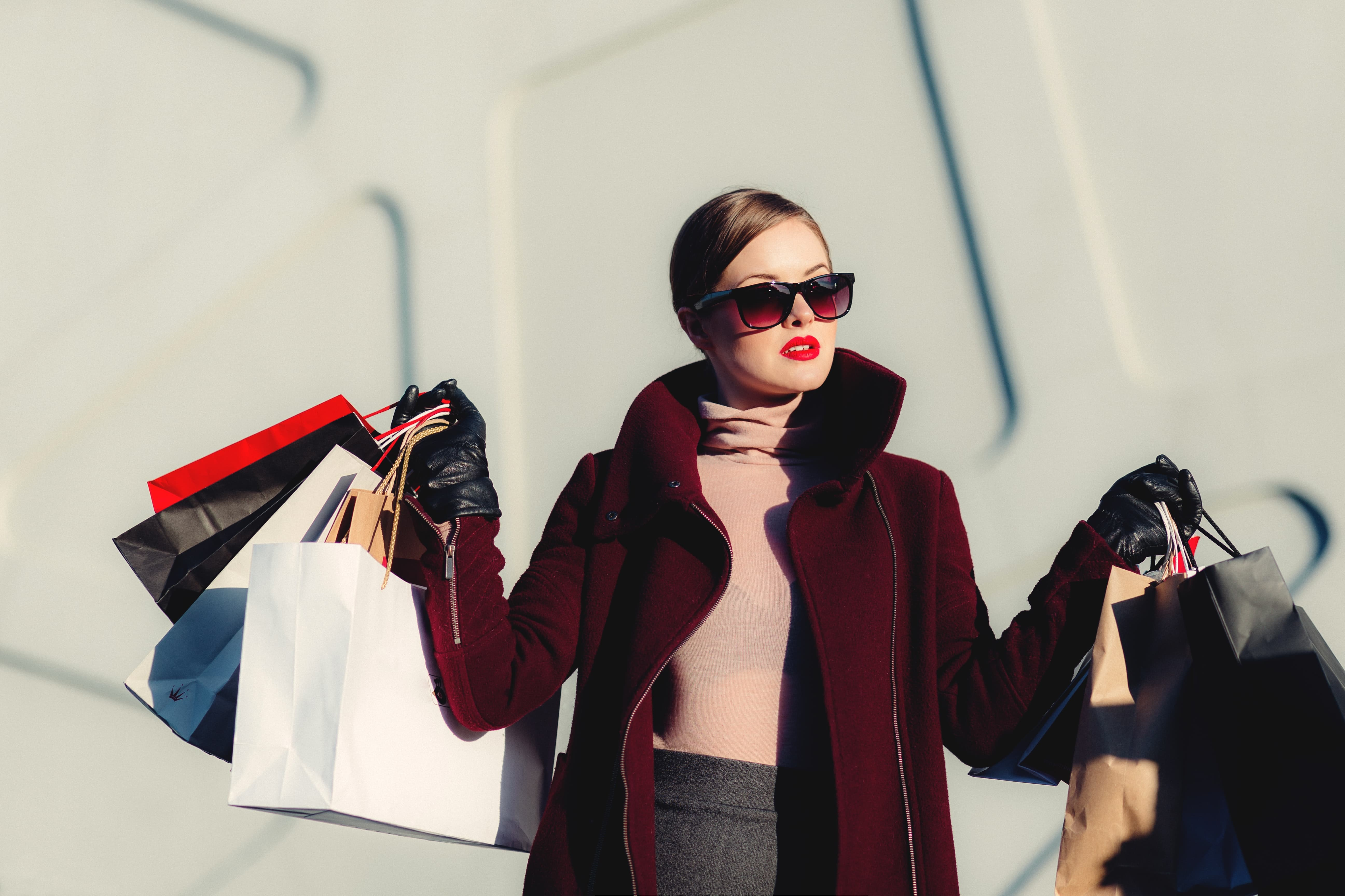 woman in sunglasses carrying shopping bags