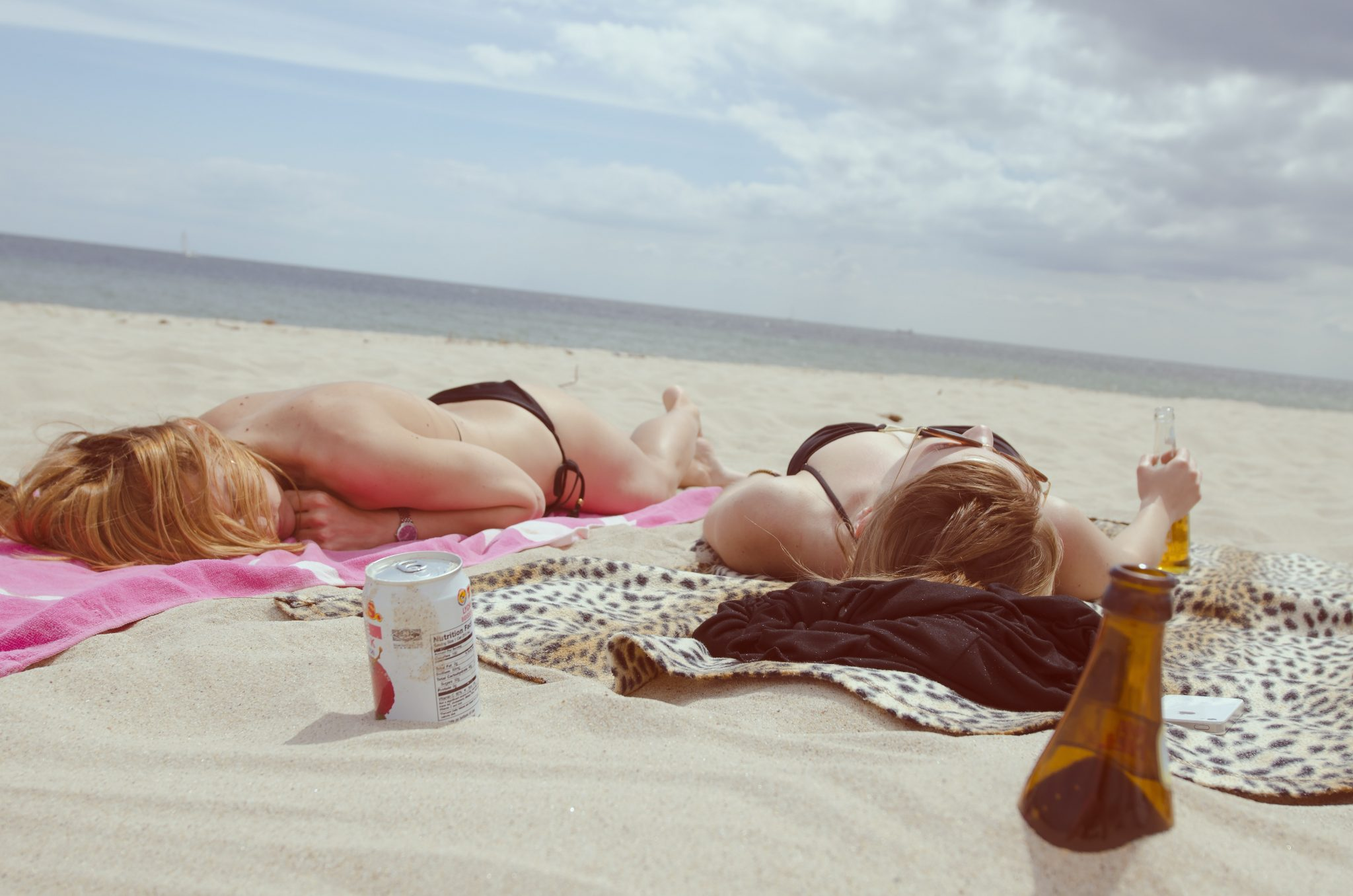 two women sunbathing on the beach having drinks