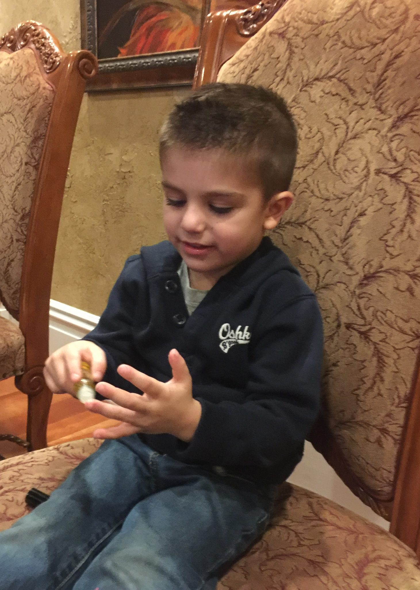 little boy sitting in chair applying essential oils to his fingers
