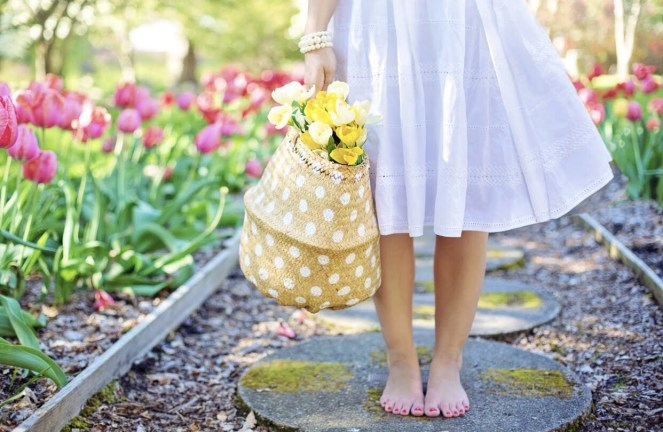 barefoot woman who has just had reiki holding flowers
