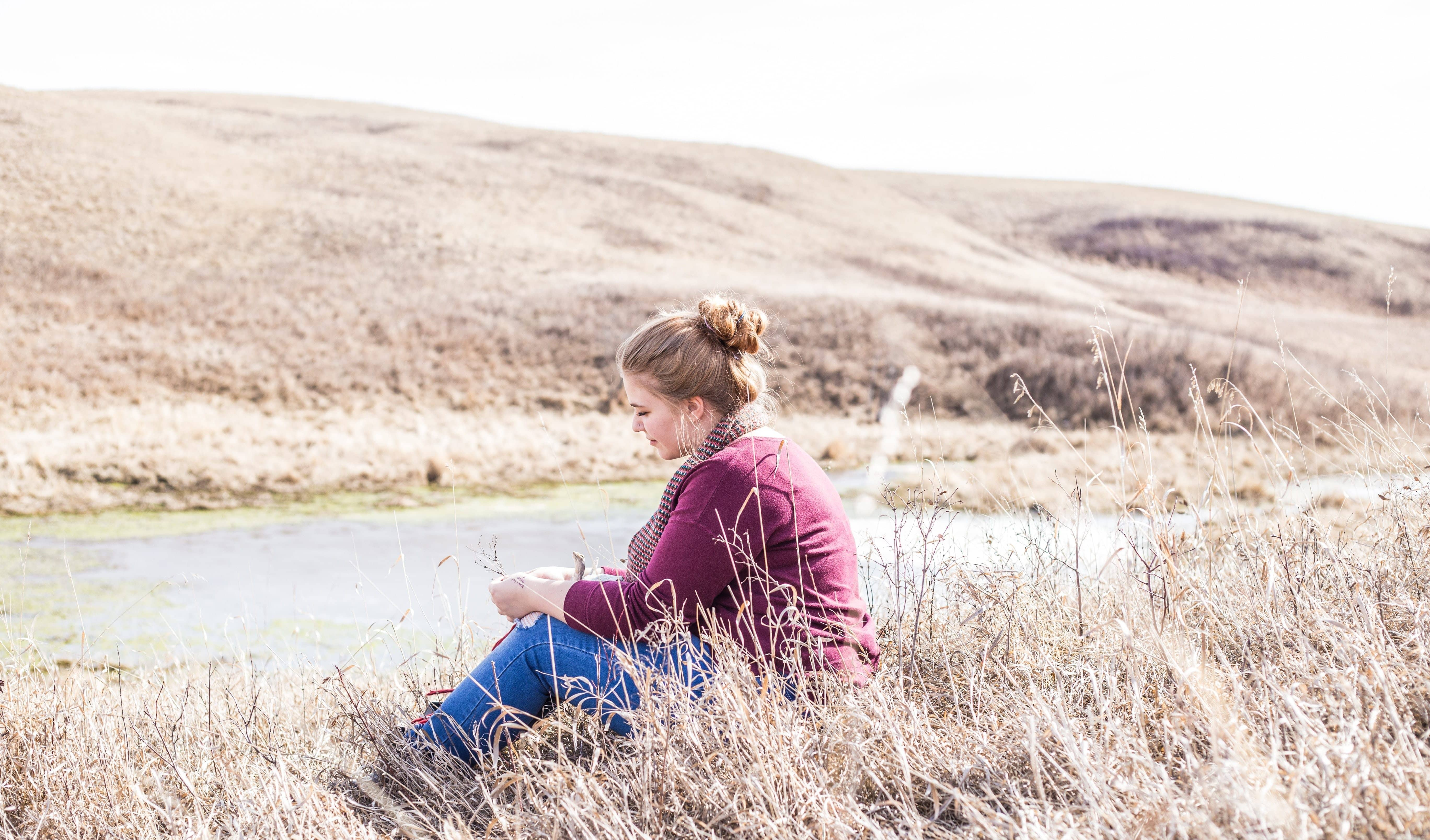woman in red sweater sitting in a field