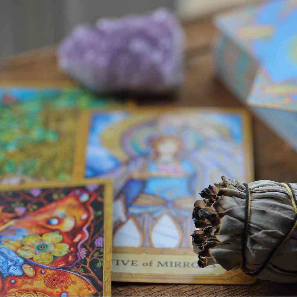tarot cards and sage bundle on table