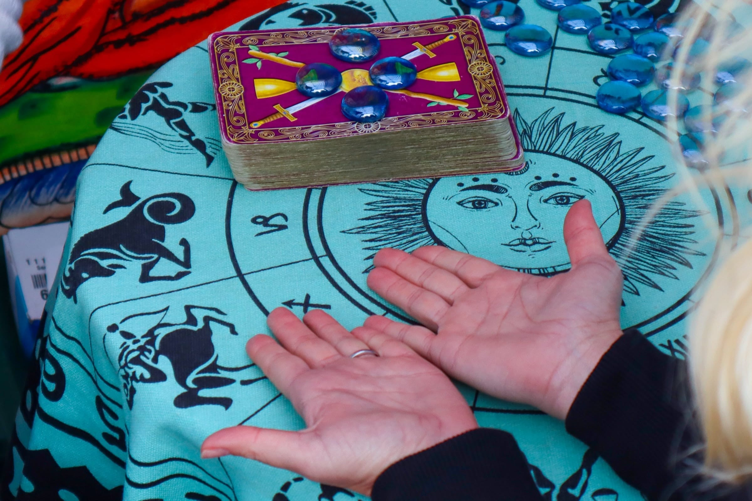 woman's hands with palms face up on a table in front of a deck of tarot cards
