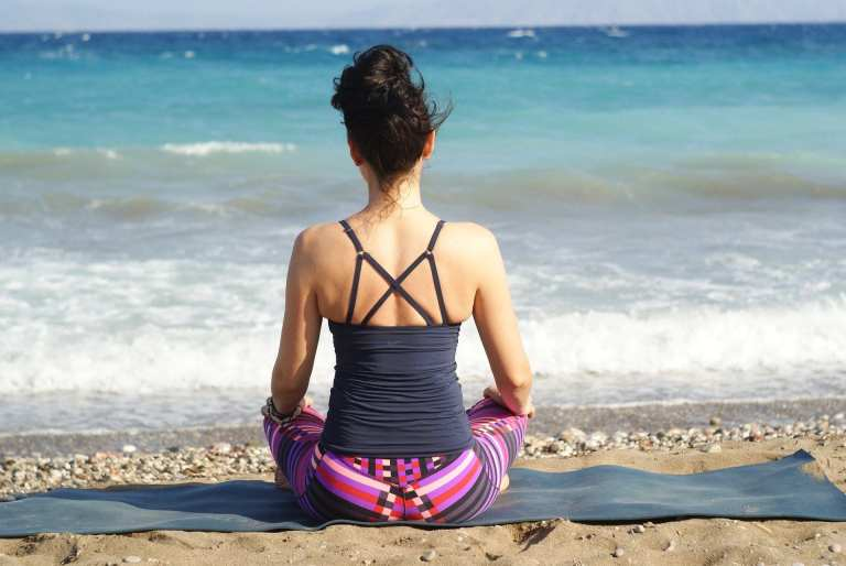 woman sitting on a yoga mat at the beach