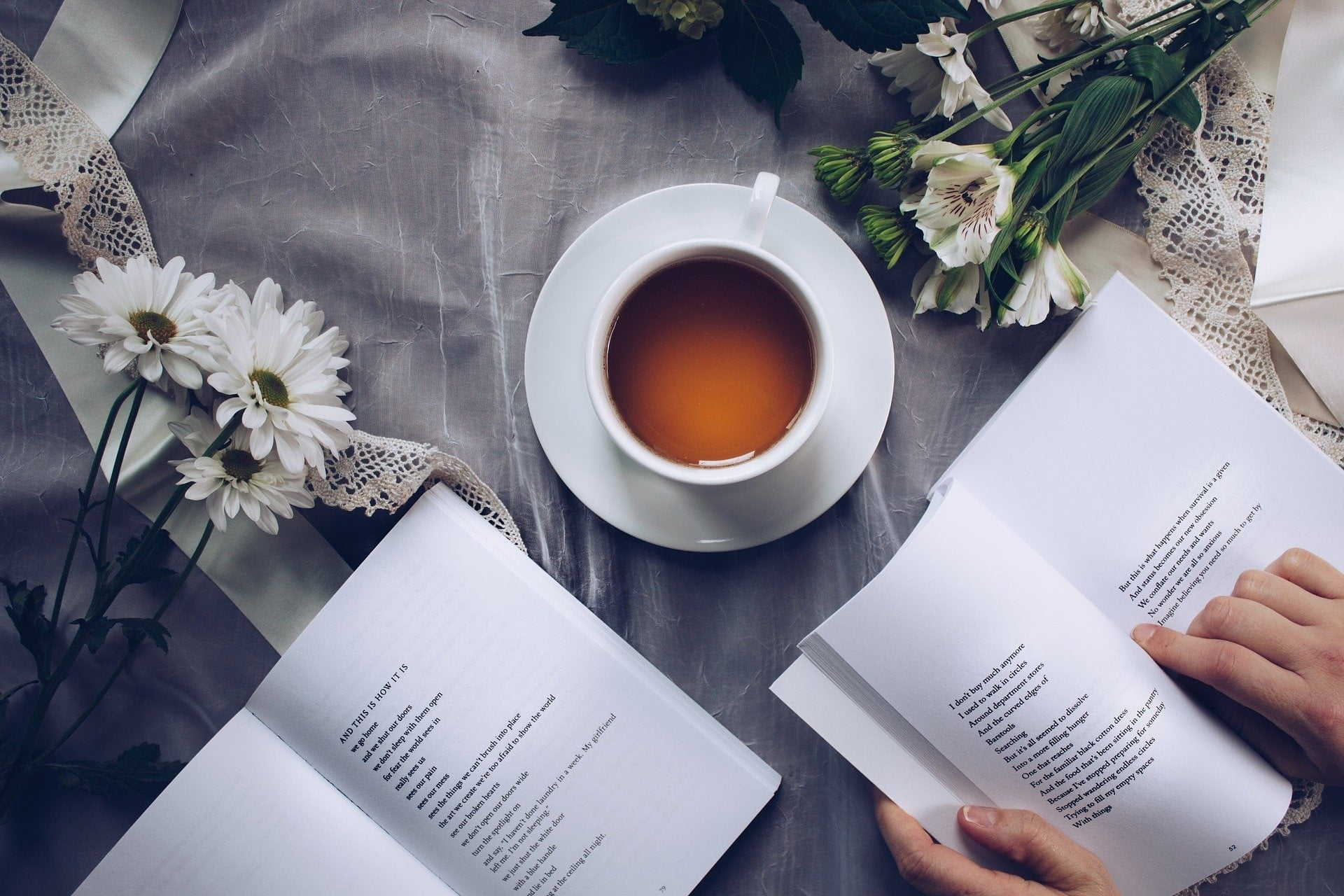 open poetry book on a table with a cup of tea and flowers