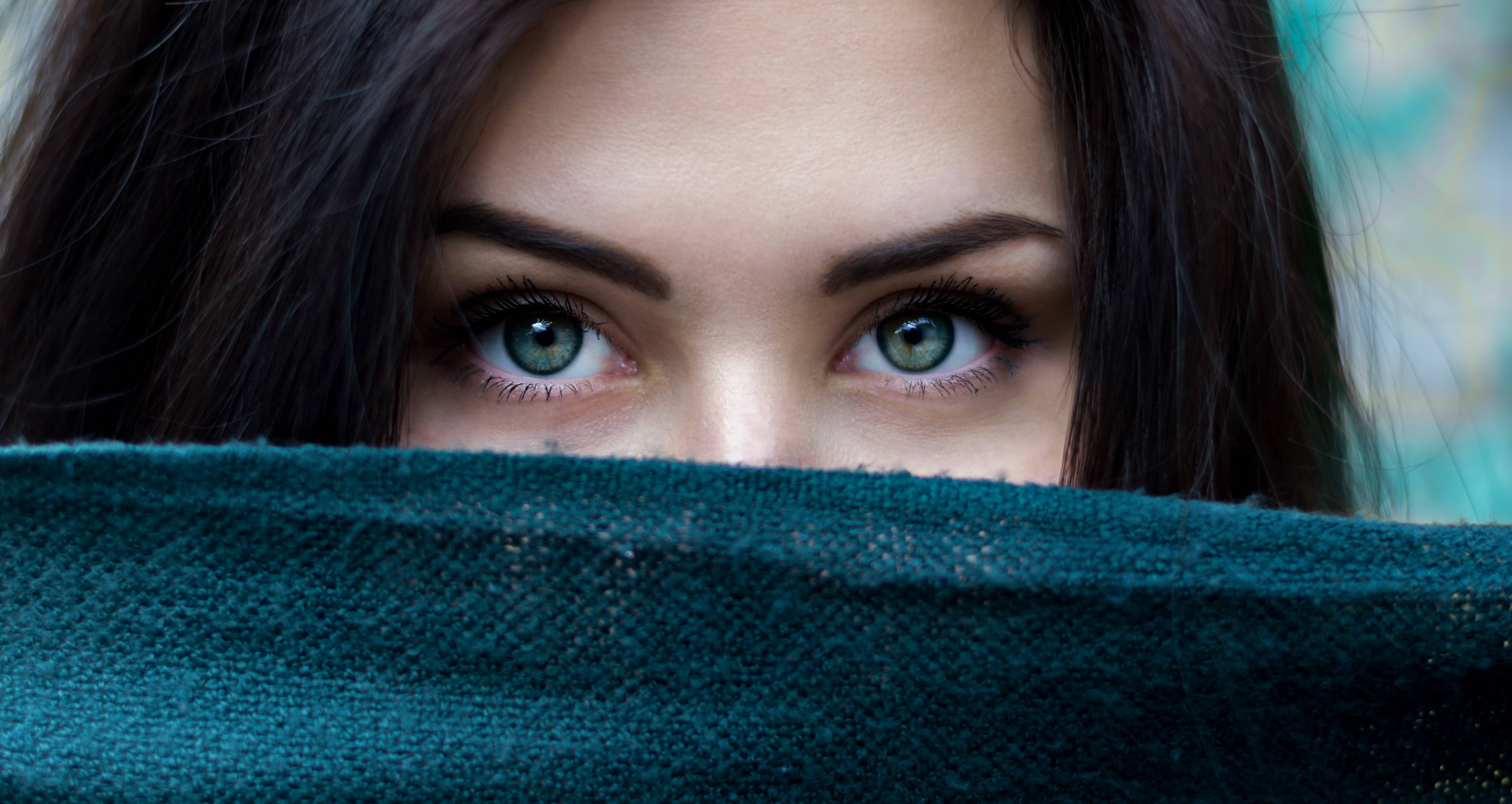 woman with blue eyes with a blue scarf covering her nose and mouth