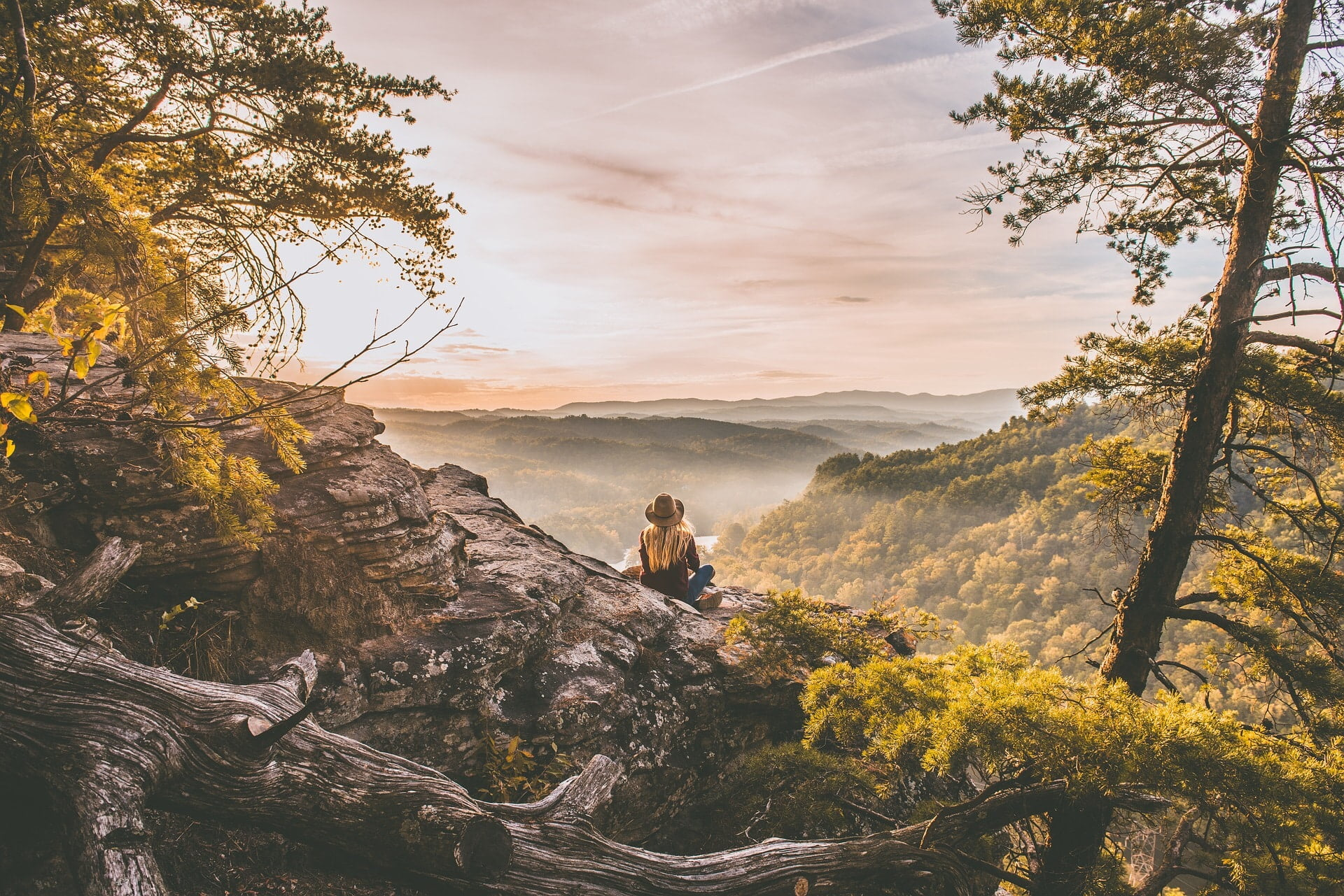 woman wearing a hat sitting alone at the top of a mountain